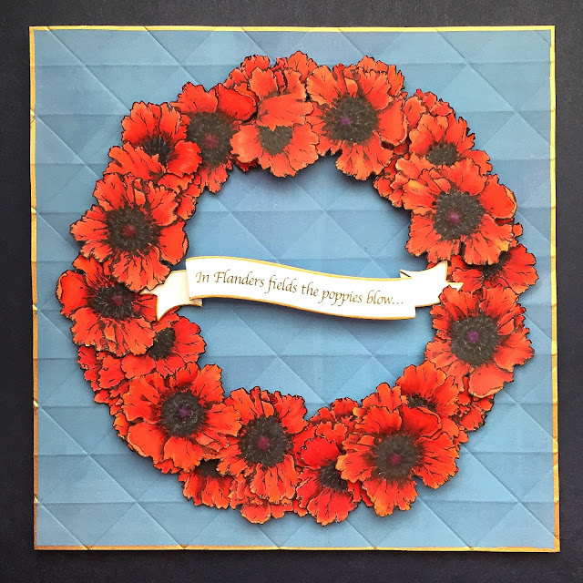 Red poppies wreath on blue background, against a Navy ground.  Gold borders on card and banner.