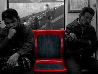 Dos hombres sentados en un tren, un asiento entre ellos