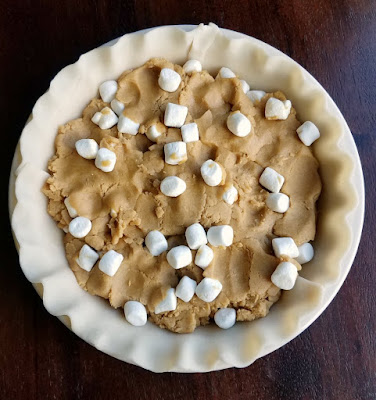 peanut butter cookie dough and mini marshmallows pressed into pie crust ready to bake