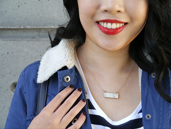 Details: sherpa/shearling collar, gold and marble-like howlite necklace, vampy nails, red lipstick