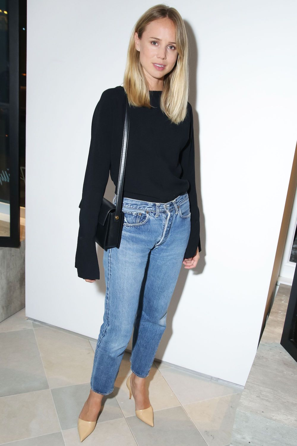 Effortless Denim Spring Outfit — Elin Kling in a black flare sleeve top, black shoulder bag, straight-leg jeans, and beige heels