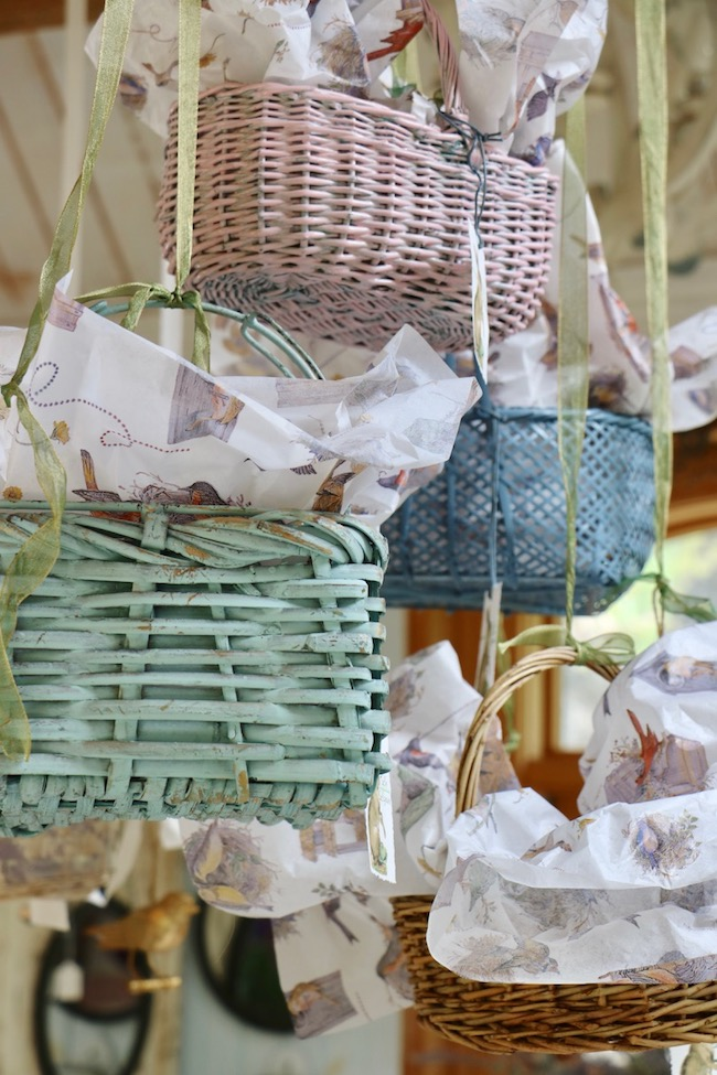 Spring baskets in pastel colors hang from the ceiling at different heights and angles  in the garden shed