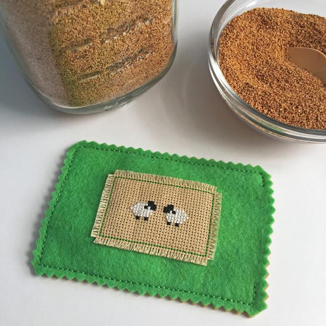 Sewing cross-stitched felt pincushion.