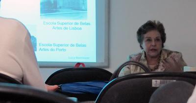 Foto de Lucy Niemeyer durante um seminário. Ela esta sentada em uma mesa em frente a uma tela de projeção.