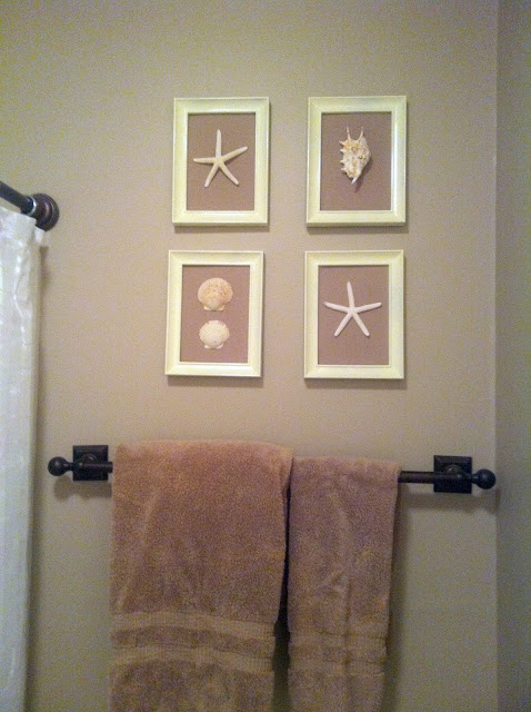 A finished picture of four white picture frames with shells inside of them as decor in a bathroom