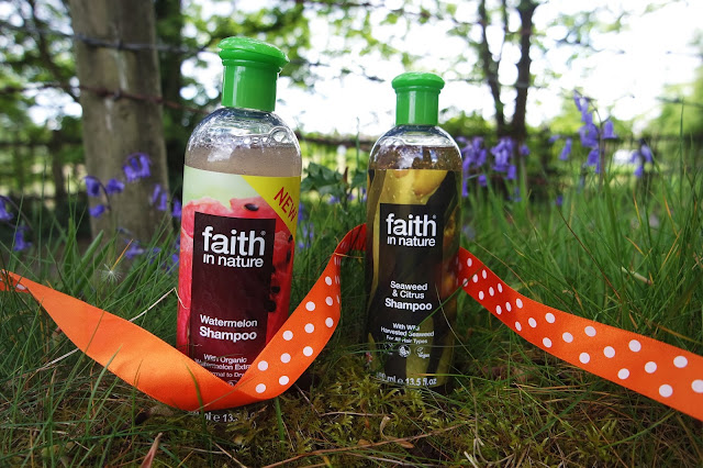 faith in nature watermelon and seaweed and citrus shampoos propped up in grass with bluebells behind them