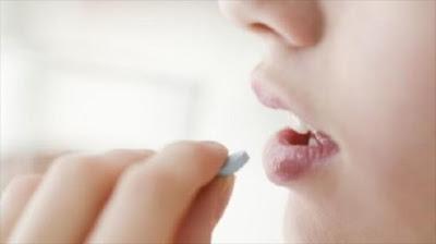 Una mujer tomando una aspirina.
