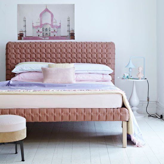 A quilted bed in a pretty pastel color.