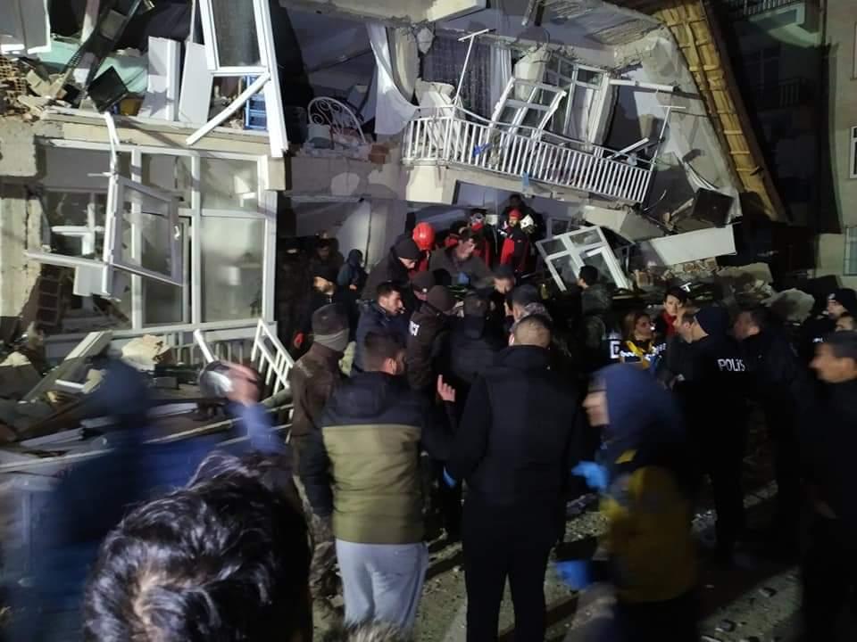 Glābēji un aculiecinieki pulcējušies pie sabrukušas ēkas un vēro glābēju darbu