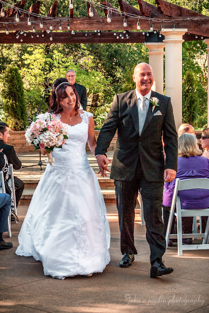 A very happy Bride and Groom walk down the isle at their outdoor wedding in Colorado