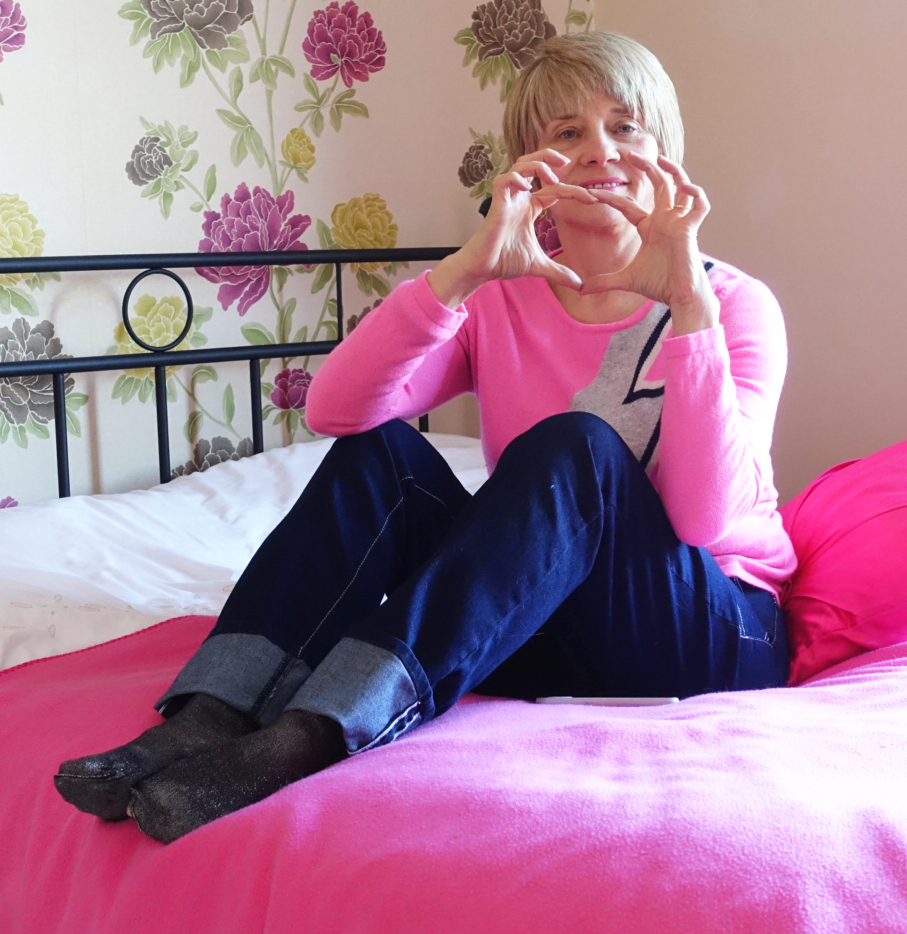 Image showing a woman over 45 in a bedroom holding her hands in a heart shape. The picture illustrates an article on blog Is This Mutton? about how to stay healthy and active to avoid heart disease in early middle age.
