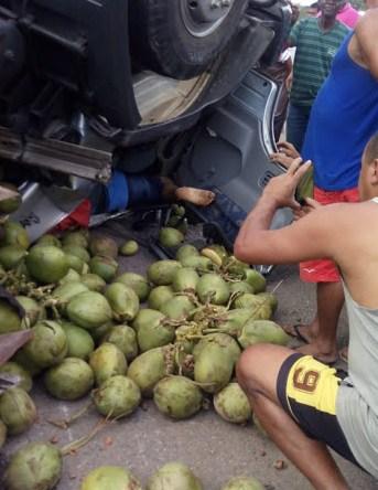 Caminhão baú carregado de coco capota e deixa dois feridos