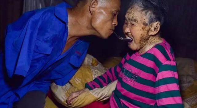 Безрукий инвалид кормит мать, прикованную к постели, держа ложку в зубах