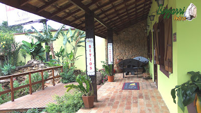 Parede de pedra, com pedra moledo, ma cor de pedra cinza mesclado na construção de cabana rústica com o piso de tijolo de demolição, o deck de madeira com execução do paisagismo.