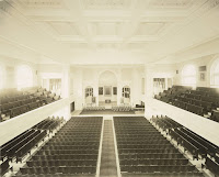 A photograph of Webster Hall during its time as an auditorium, with rows of seats and an elevated stage.