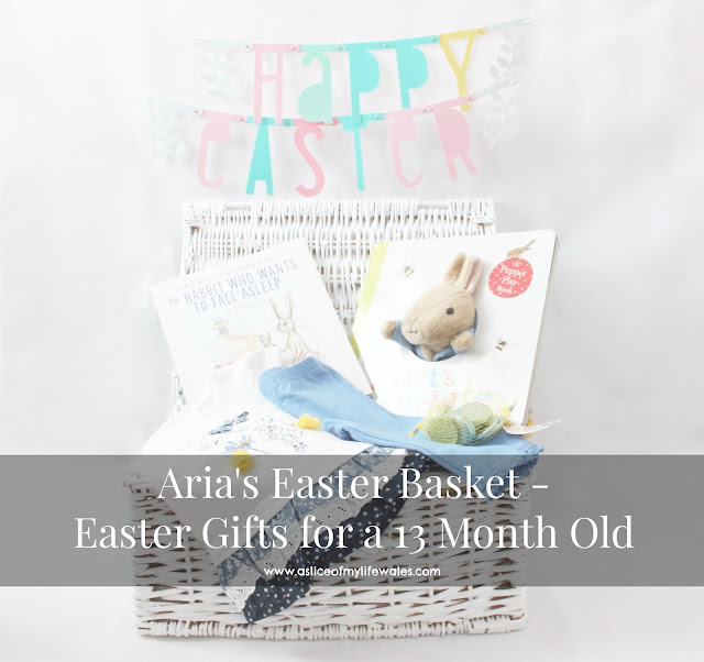 an easter gift guide for a thirteen month old baby a white basket containing books clothing and a token gesture of white chocolate coins