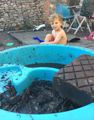 Picture of my son with his mud pie he made in his water play table