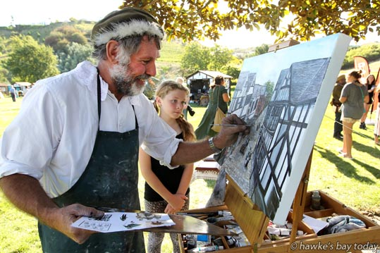 Grant Hughes, artist, Napier, painting a town scene from the Elizabethan Period, watched by Meaghan Broad, 10, Havelock North - Much Ado about Nothing, at Shakespeare in the Park, at Church Rd Winery, Taradale, Napier. photograph