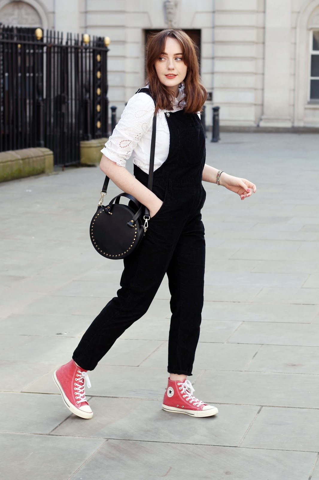 Liverpool style blogger wearing white broderie anglaise blouse under topshop black corduroy dungarees, black circle bag and washed red hightop converse