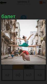 Девушка в воздухе на улице показывает шпагат как в балете