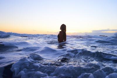 Chica de pie en el mar mirando al cielo al atardecer