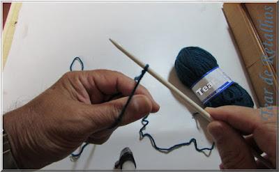 Foto mostrando o inicio da montagem à italiana da base de pontos do trico. Colocando os dedos polegar e indicador entre as pontas dos fios que saem da agulha.