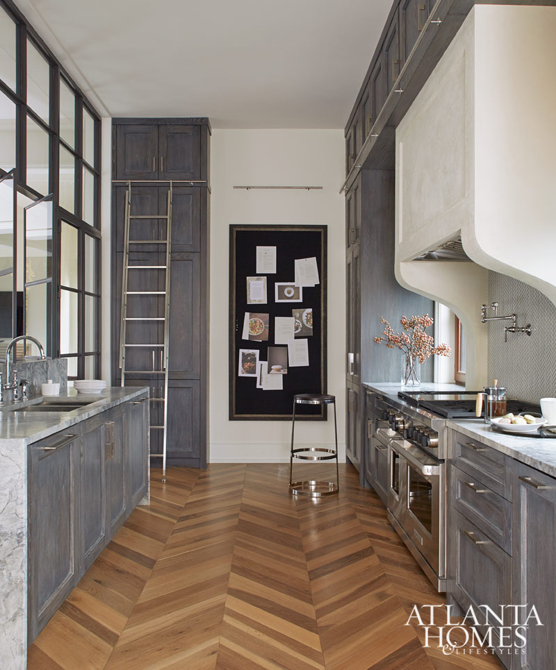 Stunning kitchen with grey cabinets, herringbone floor, and ladder