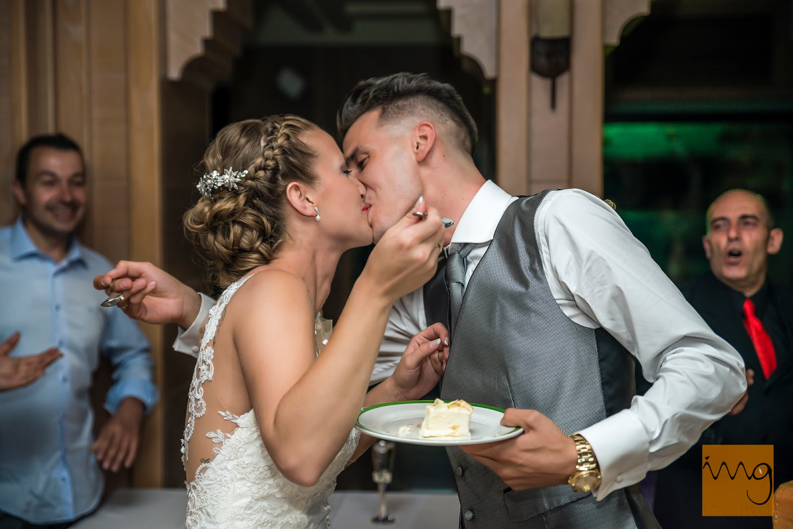 Fotografía de los novios dándose un beso en el momento del corte de la tarta.