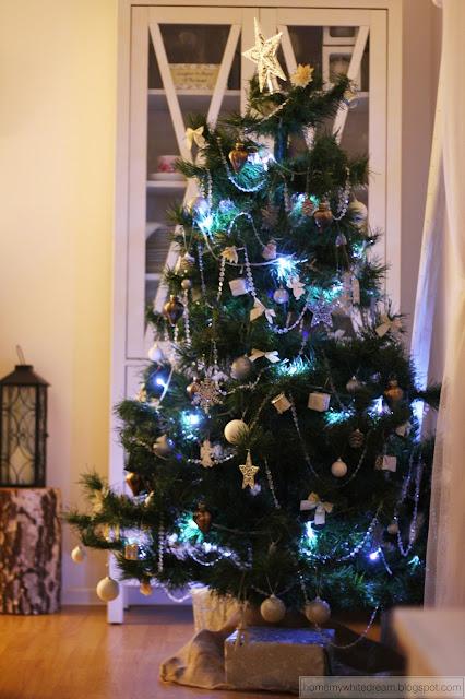 dekoracje świąteczne, choinka, biały salon, drewniana ściana w salonie, drewniane domki,