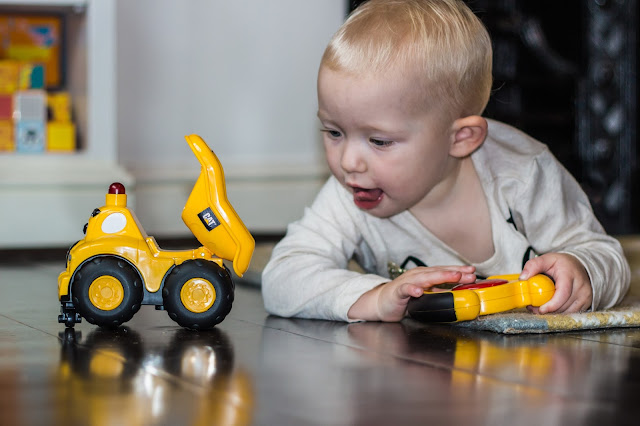side view of a yellow CAT tipper truck and a child lying on the floor with a remote control