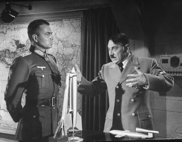 Rommel (James Mason) listens while Hitler (Luther Adler) explains how the new V weapons will win the war