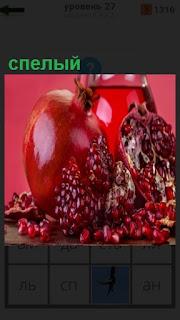 на тарелке лежит красный спелый гранат с зернами