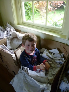 My son sitting in a packing box with lots of paper by a window in the dining room, after moving day when we moved to the country