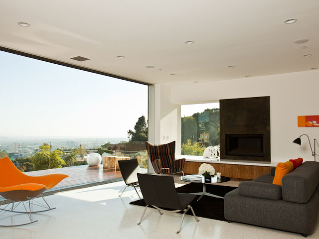 Picture of the living room with black painted fireplace, orange swaying chairs and beautiful city views