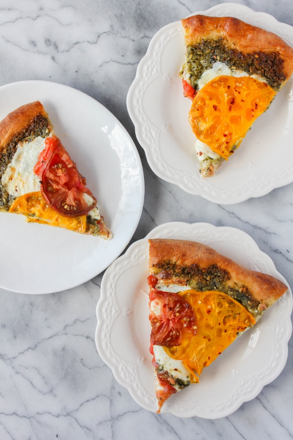 Fresh heirloom tomatoes and fresh mozzarella cheese are the stars of this beautiful Heirloom Tomato Pesto Pizza. It's a simple pizza, yet so delicious, and perfect for the summer!