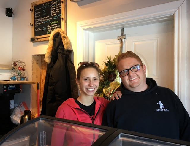 woman and man smiling behind the counter of a coffee shop