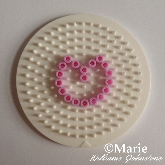 Adding the cherry pattern outline with pink perler beads on circle pegboard