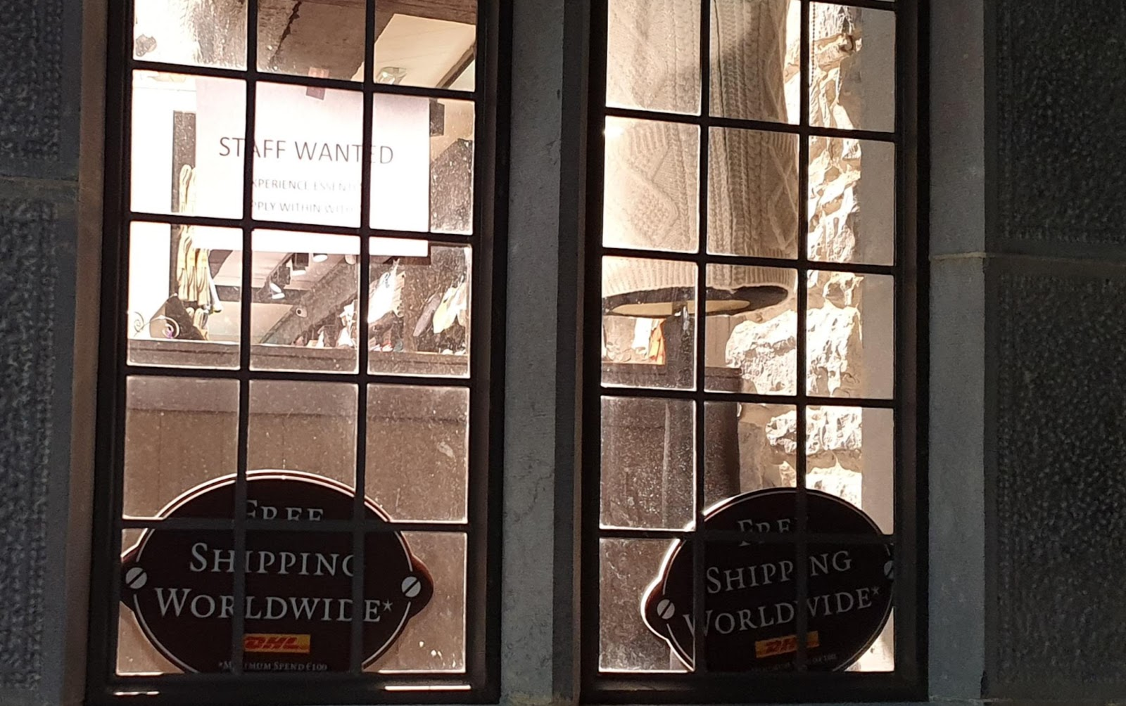 circular rugby-ball shaped free shipping worldwide signs in a shop with restored leaded glass and a staff-wanted sign
