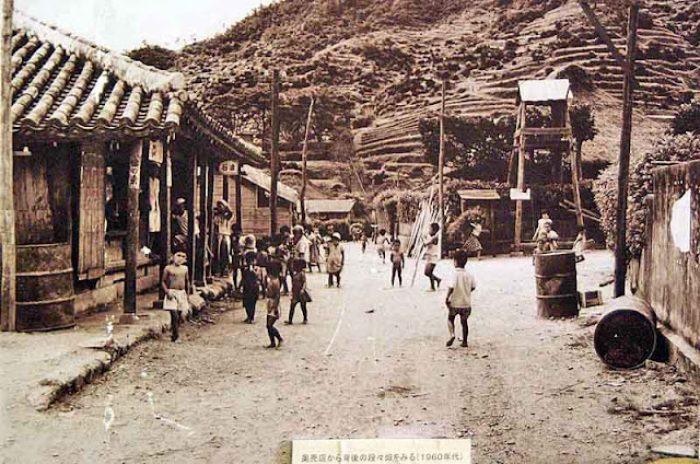 B&W photo showing village, traditional homes and terraced hills
