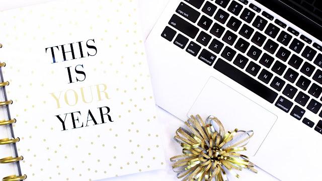 """Primer plano de un teclado de portátil y una agenda con el texto """"Este es tu año"""" en inglés"""