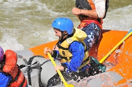Young child having a huge smile rafting with his family.
