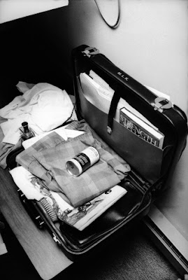 Black and white photo of an open briefcase with folded pajamas and a can of shaving cream on top