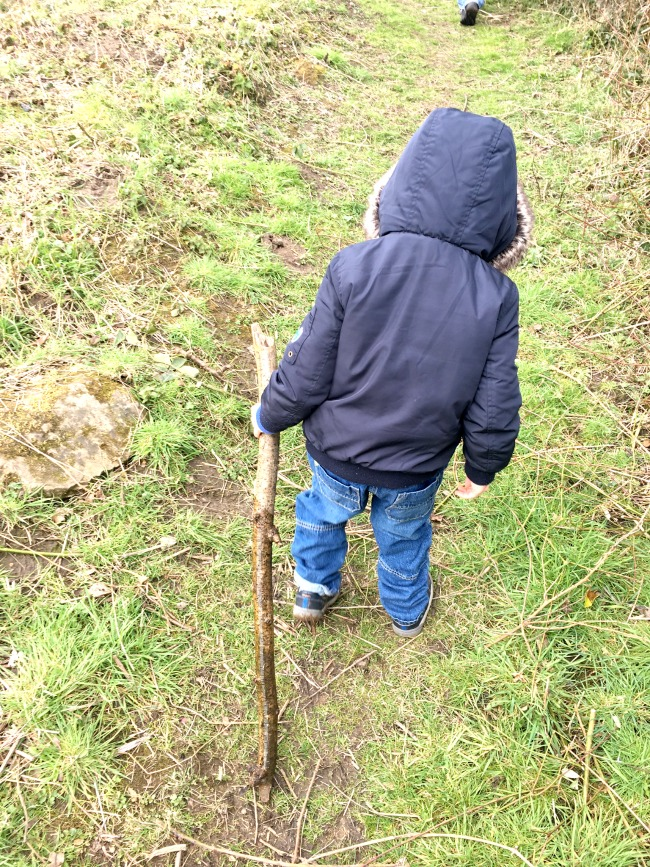 boy-walking-dragging-a-stick-behind