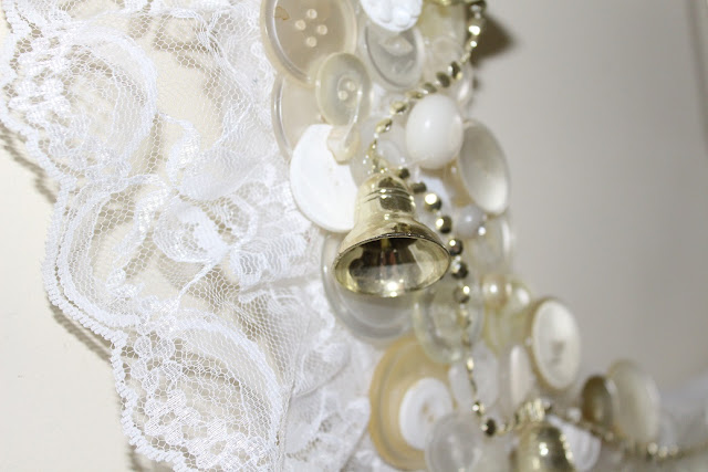 white lace, white buttons, gold bells on wreath