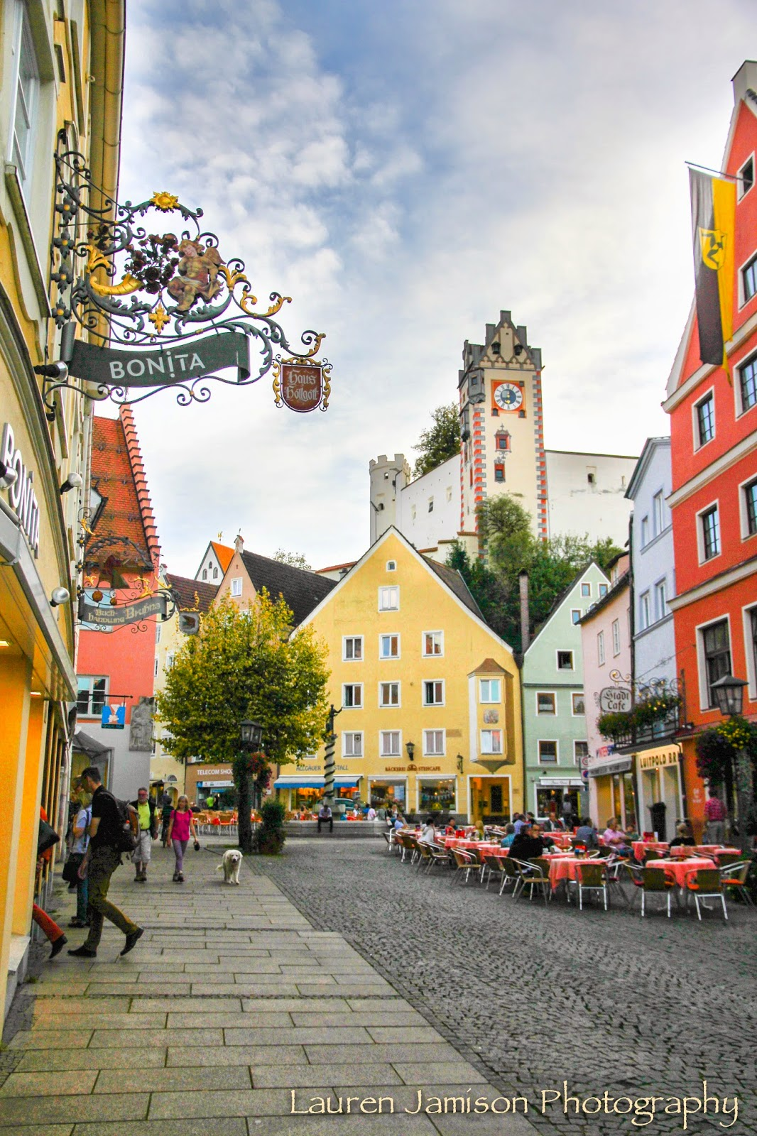 Neuschwanstein Castle & Fussen, Germany - The Lauren Jamison Collective.  Where to travel in Germany. Fairytale German towns. Pretty european wood door surrounded by yellow stucco walls.