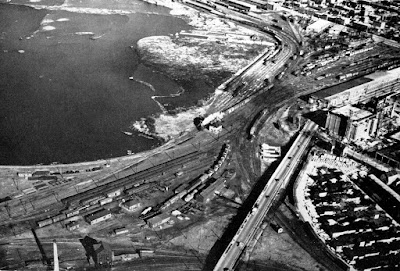 Aerial photo looking at the railyards at Bayview and Nepean Bay, with the Wellington viaduct at the bottom and some industrial buildings and lumber yards at the right (in the location of the City Centre building). The Canada Atlantic Railway no longer crosses Wellington Street.