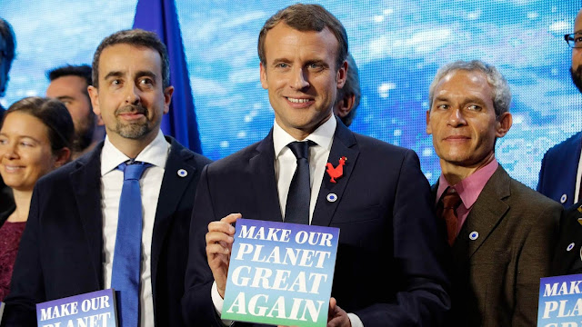French President Emmanuel Macron holds a sign with the slogan 'Make our planet great again' ahead of the One Planet Summit in Paris on December 11, 2017.