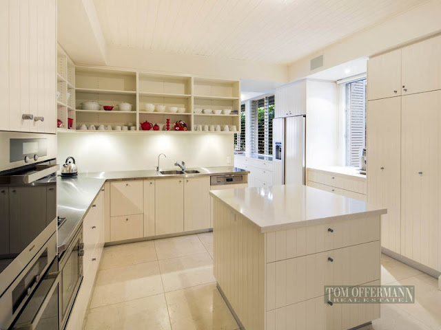 Photo of modern white kitchen with small kitchen island in the middle