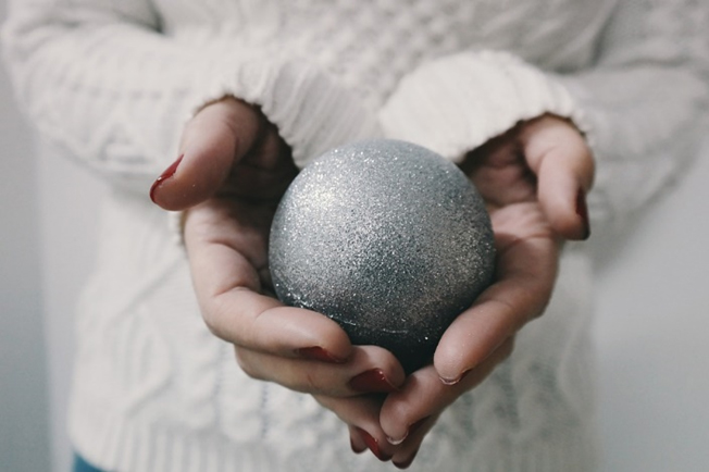 Woman in white jumper holding silver Christmas bauble