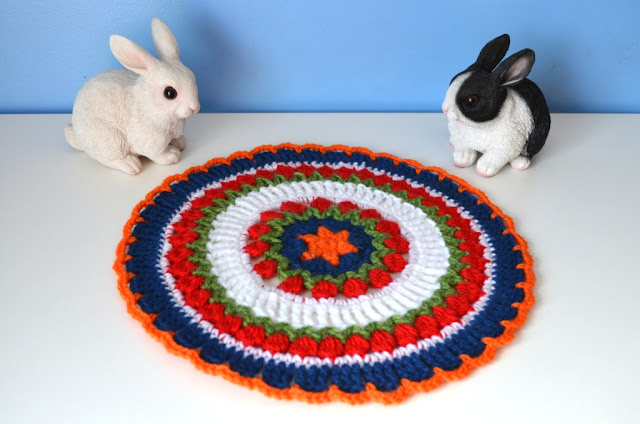 Two resin model bunnies flank the mandala made in Dutch colours: orange, red, white and blue.  Rings of red cluster stitches represent tulips with a touch of green beneath them for the foliage.